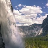 Yosemite Falls and valley against cloudy blue sky royalty free stock images