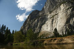 Yosemite National Park, California, USA. Steep mountain cliff, forest and grass meadow, stream, clear sky with a patch of cloud Stock Photography