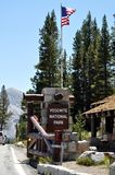 Yosemite National Park entrance. Yosemite National Park (California's Sierra Nevada mountains) - Entrance of the park, with sign and United States flag Royalty Free Stock Photos