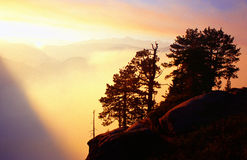 Yosemite sunset. USA- Yosemite, sunset over clouded moutains and tree Stock Photos