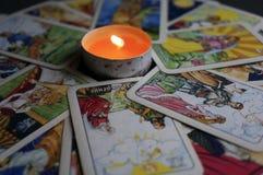 YOSHKAR-OLA, РОССИЯ - 13-ОЕ НОЯБРЯ 2017: Удача говоря на карточках Tarot на черной предпосылке с горящей свечой стоковая фотография
