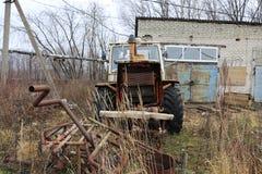 YOSHKAR-OLA, RUSIA - 23 DE NOVIEMBRE DE 2017: Un tractor oxidado abandonado viejo con un motor de trabajo Foto de archivo libre de regalías