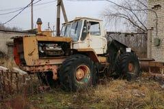 YOSHKAR-OLA, RUSSLAND - 23. NOVEMBER 2017: Ein alter verlassener rostiger Traktor mit einer Arbeitsmaschine lizenzfreies stockfoto