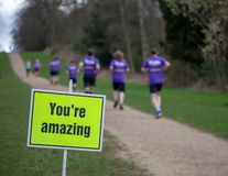 You`re amazing sign post with runners for charity on a path stock image