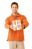 For You. Portrait of a mature adult man wearing an orange sweater and khakis holding a gift isolated on white isolated on white stock photography