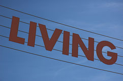 Are you?. The word 'living' strung across a blue sky background Royalty Free Stock Photography
