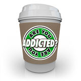 Are You Addicted to Coffee or Caffeine Cup Addiction Treatment. Are You Addicted words in a question on a coffee cup asking if you have an addiction to caffeine Royalty Free Stock Image