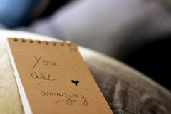 You are amazing handwritten on a cover notebook. On the couch in the living room. love Hand written memo message with heart on the cover of a note pad stock images