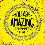 You are  amazing. remember that. Inspirational quotes. Written in a wreath by hand, for writing on posters, T-shirts and cards. Vector calligraphy, isolated on Stock Images