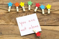 Free You Are Not Alone Message Card Handwriting With Colorful Wooden Star Clips Arrangement Flat Lay Postcard Style Royalty Free Stock Photography - 161234497