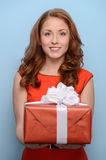 This is for you. Attractive young woman holding a gift box in he Royalty Free Stock Photos