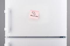 You are beautiful note on pink paper on white refrigerator Stock Photo