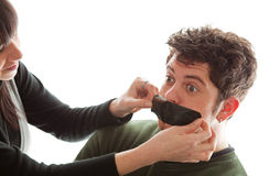 You better shut up my dear!. Girl sticking a piece of gaffer tape on young man's mouth Royalty Free Stock Photography