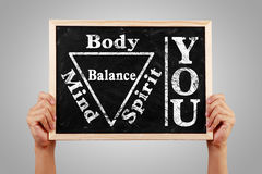 You Body Spirit Soul Mind Balance. Hands holding blackboard with text You Body Spirit Soul Mind Balance against gray background Stock Photo