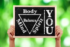 You Body Spirit Soul Mind Balance. Hands holding blackboard with text You Body Spirit Soul Mind Balance against green blurred background Stock Image
