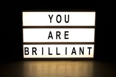 You are brilliant light box sign board. On wooden table Stock Photo