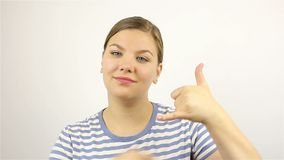 You call me. gesture. Young beautiful woman. On a grey background stock video footage