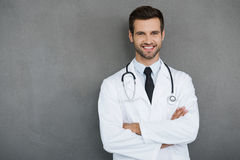 You can absolutely trust me. Confident young doctor in white uniform looking at camera and keeping arms crossed while standing against grey background royalty free stock images