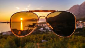 Sunset at seaside, captured in sunglasses. You can clearly see the sun trought the sunglasses. Photo was taken on a Croatian coast stock image