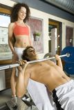 You can do it!. Young couple, working out in gym. Man is lying on bench and picking up dumbbell. Woman is standing behind him. Side view Royalty Free Stock Images