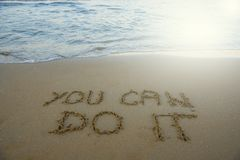 You can do it. Motivational inspirational message concept written on the sand of beach. royalty free stock photo