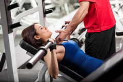 You can do this. Personal trainer helping a young woman lift a barbell while working out in a gym Royalty Free Stock Photos