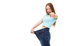 You can do it! Young slim woman with large jeans pointing finger Royalty Free Stock Photos