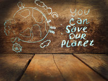 You can save our planet. On wood Background Stock Photo