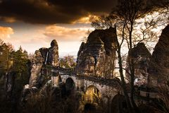 Old sandstone bridge in a german national park with an amazing v. You can see a sandstone bridge with some rocks in a beauriful orange sunset Royalty Free Stock Images