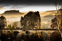 Old sandstone bridge in a german national park with an amazing v. You can see a sandstone bridge with some rocks in a beauriful orange sunset Stock Image