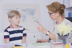 You can't forget about your homework!. Shot of a strict teacher pointing finger and giving a little student reprimand royalty free stock image
