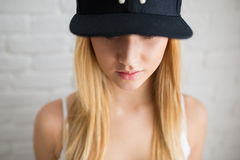 You can't see my eyes. A photo of young woman wearing black cap which covers her eyes Stock Photo