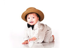 Funny smiling baby in in suit, retro hat and a bow-tie, crawling over white background stock images