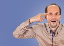 You are crazy. Young man gesturing with his finger against his temple. on blue color background stock images