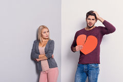 You destroyed our love. What I have done. Young men is holding torn heart and touching head with regret. Young women is standing and looking at him with offence Royalty Free Stock Photo