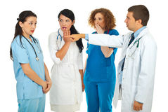 You did it!. Hospital manager accusing  doctor woman and pointing and her colleagues doctors women being surprised and scared isolated on white background Stock Photography