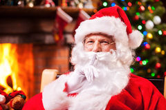 You did not see me!. Traditional Santa Claus gesturing silence sign while sitting at his chair with fireplace and Christmas Tree in the background Royalty Free Stock Photos