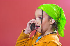 You don' say?!. Surprised young girl with green kerchief talking on a mobile phone Royalty Free Stock Photo