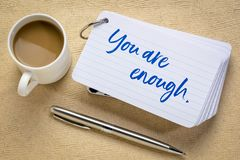 You are enough concept. Handwriting on a stack of index cards with a cup of coffee and a pen against textured bark paper stock photography