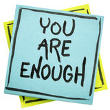 You are enough inspirational concept. Handwriting in black ink on an isolated sticky note stock photo