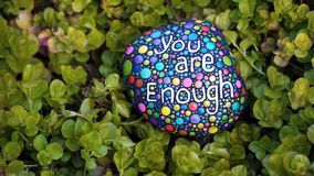 You Are Enough. The words you are enough kindness message colorfully hand painted with dots on a rock, in a bed of green groundcover royalty free stock image