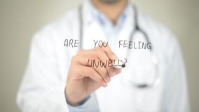Are You Feeling Unwell ? , Doctor writing on transparent screen. High quality Royalty Free Stock Images