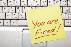 'You are Fired!'. Yellow sticky note on a laptop keyboard with 'You are Fired!' on it Stock Photos