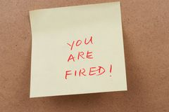 You are fired. Words on sticky note attached on the board Royalty Free Stock Photography