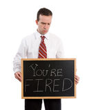 You Are Fired. A young teacher looking down at his chalk board which says you're fired, isolated against a white background Stock Photos