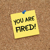 You Are Fired!. Adhesive note pinned on cork noticeboard Royalty Free Stock Photo