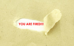 YOU ARE FIRED. Text YOU ARE FIRED appearing behind torn light brown envelope Royalty Free Stock Photography