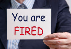 You are fired. Text on a white card held by a smartly dressed businesswoman saying 'you are fired' with 'fired' emphasized by being written in red uppercase Stock Photos