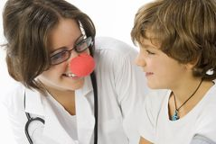 You are so funny. Young and cute female doctor with a red nose visiting a little boy royalty free stock photos
