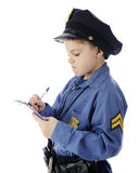 You Get a Ticket for That!. A young elementary policeman intently writing a ticket.  On a white background Royalty Free Stock Image